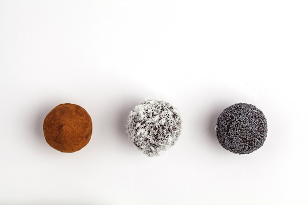 Homemade healthy vegan raw energy balls with carob, poppy and coconut isolated on white background, top view