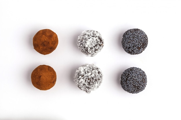 Homemade healthy vegan raw energy balls with carob, a poppy and coconut isolated on white background, top view