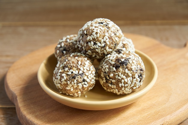 Homemade healthy vegan raw energy  balls with sesame on wooden cuttng board.
