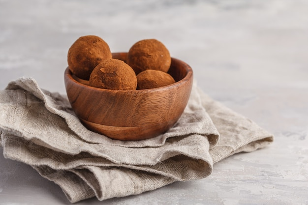 Homemade healthy vegan raw energy truffle balls with carob in wooden bowl. healthy vegan food concept.