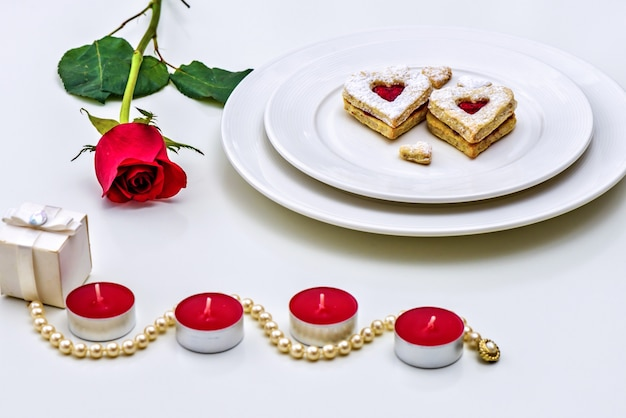 Homemade heart shaped almond linzer cookies on white plate