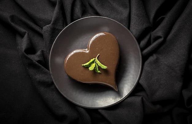 黒の背景に自家製ハート型チョコレートケーキ