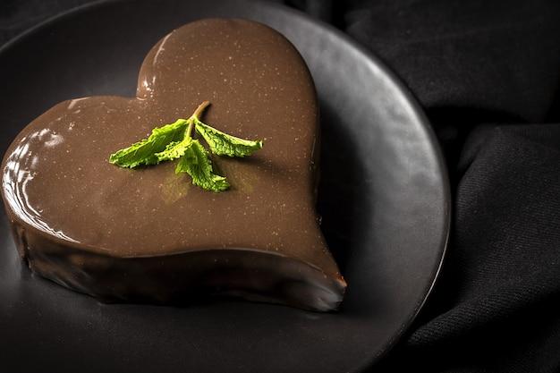 Домашний шоколадный торт в форме сердца на черном фоне