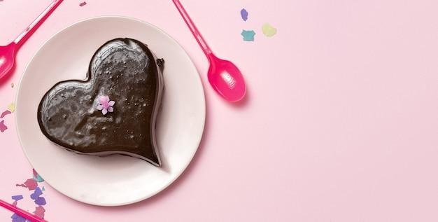 色の背景に自家製ハート型チョコレートケーキ