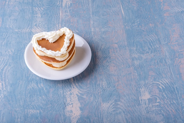 Домашний блинчик в форме сердца с бананом, украшенный белым кремом, на белой тарелке на синем деревянном столе