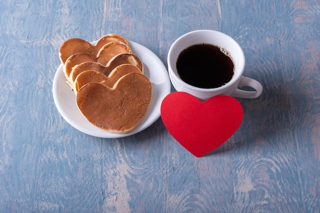Homemade heart shaped pancakes on a white plate, a mug with coffee or cocoa and a red blank heart shape on a blue stylish wooden background