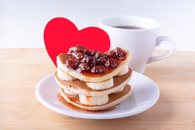 Homemade heart shaped pancakes with berry jam and bananas on a white plate, fork, mug with coffee or cocoa and red heart