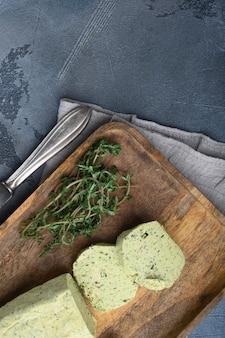 회색 돌 배경에 마늘 세트가 있는 홈메이드 허브 버터, 텍스트 복사 공간