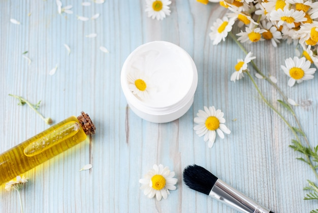 Homemade herbal cosmetics with camomile, essential oils, facial cream
