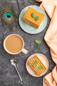 Homemade honey cake with milk cream and mint with cup of coffee on a black concrete background. top view, close up.