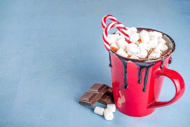 赤いマグカップの自家製ホットチョコレート、ミニマシュマロとチョコレートのしずく、キャンディケインの装飾、コピースペース