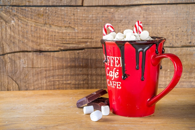 Homemade hot chocolate in red mug, with mini marshmallows and chocolate drips, candy cane decor, copy space