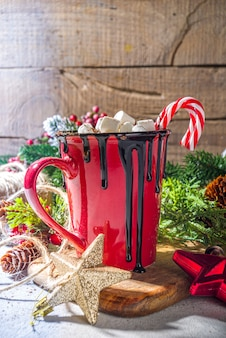 Homemade hot chocolate with mini marshmallows, hot cozy christmas cocoa drink on wooden background with xmas decorations copy space
