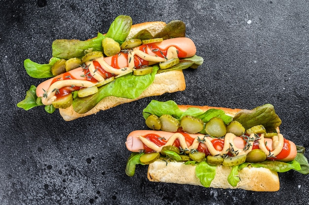 Homemade hot dogs with vegetables, lettuce and condiments. black background. top view.