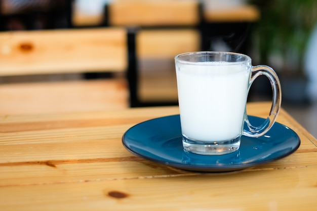 Homemade hot fresh milk in clear glass with blue saucer (bottom plate) serve on wooden table, for beverage background or texture - healthy diet concept.