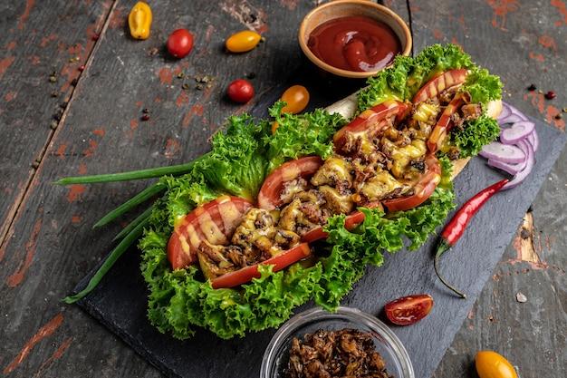 Домашний хот-дог с луком. жареное мясо, помидоры, листья салата и сырный соус. концепция быстрого питания и нездорового питания, вид сверху