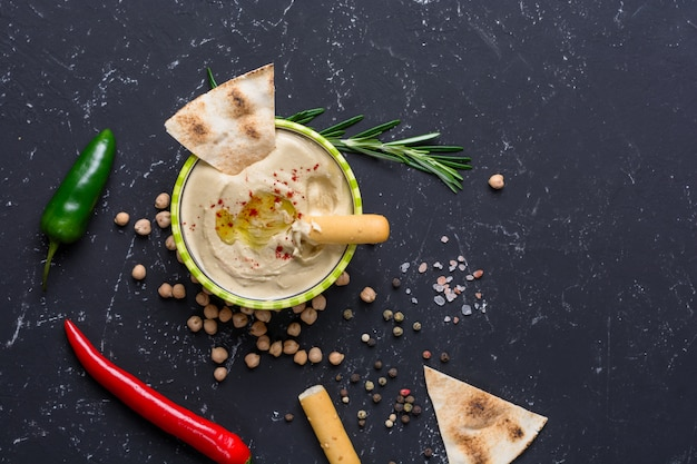 Homemade hummus with pita and grissini bread sticks, chilli, jalapeno on black stone table. middle eastern traditional and authentic arab cuisine. top view, flat lay