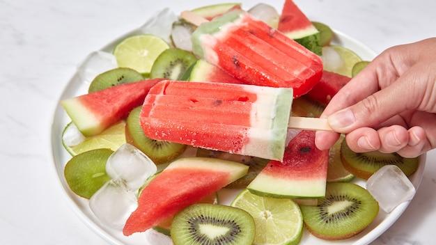 果物の切れ端が付いている棒の自家製アイスクリーム