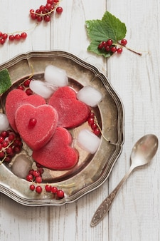 Homemade ice cream of red currant in shape of heart and on vintage dish and wooden background.
