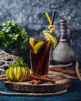 Homemade ice tea with lemon slices on wooden board