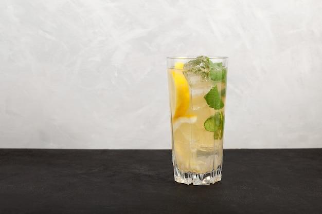 背の高いグラスに自家製アイスレモネードレモンとミントの葉でさわやかな夏の飲み物