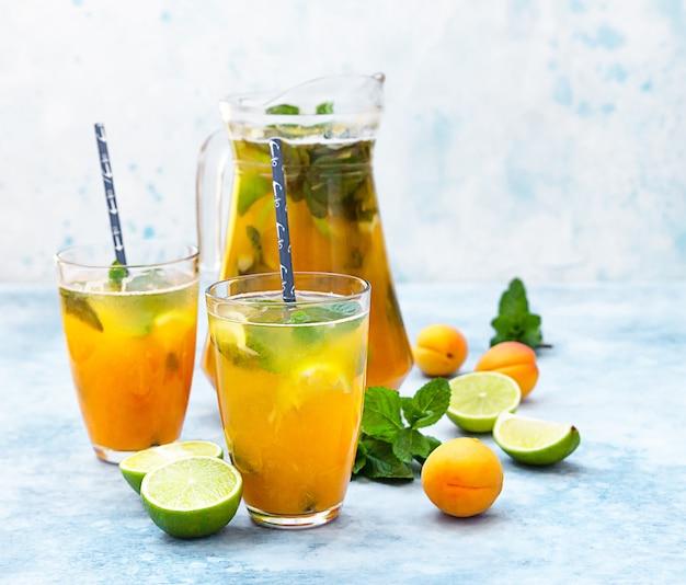 Домашний лимонад со льдом или чай с абрикосом, лаймом и мятой. свежий абрикосовый безалкогольный коктейль в кувшине и стаканах.