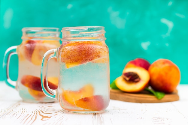 Homemade iced lemonade with ripe peaches. fresh peach ice tea in a mason jar.
