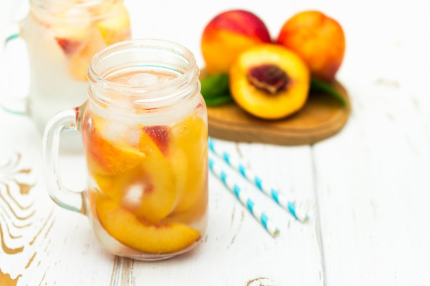 Homemade iced lemonade with ripe peaches. fresh peach ice tea in a mason jar.