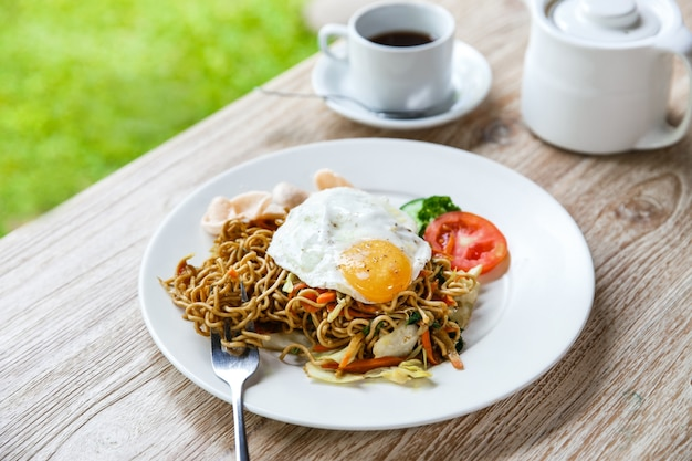 Homemade indonesian fried noodle with a cup of hot tea for breakfast