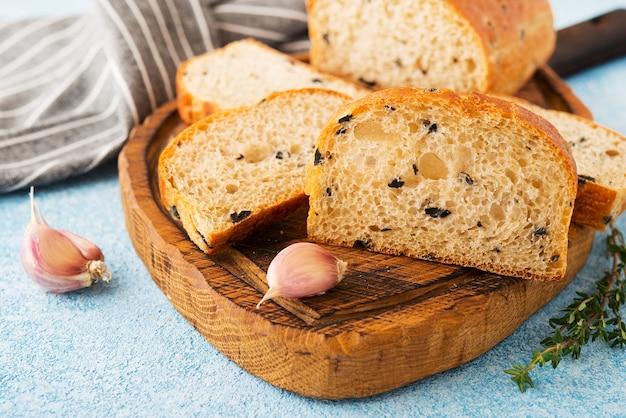 Homemade italian ciabatta bread with herbs, garlic and olives, close up