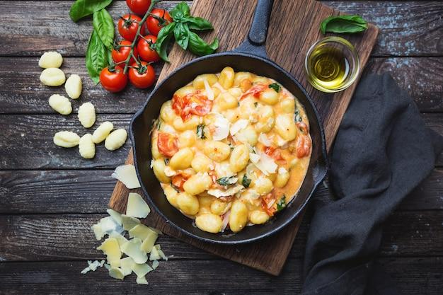 木製のテーブルにトマトガーリックバジルとモッツァレラチーズを添えた自家製イタリアンニョッキ