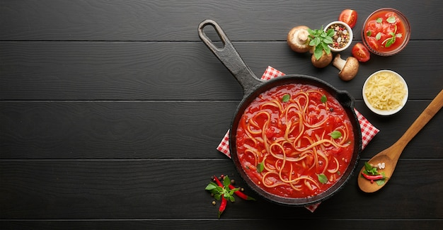 Homemade italian pasta spaghetti with tomato sauce in cast iron pan served with red chili pepper, fresh basil, cherry-tomatoes and spices over black rustic wooden table, food cooking concept