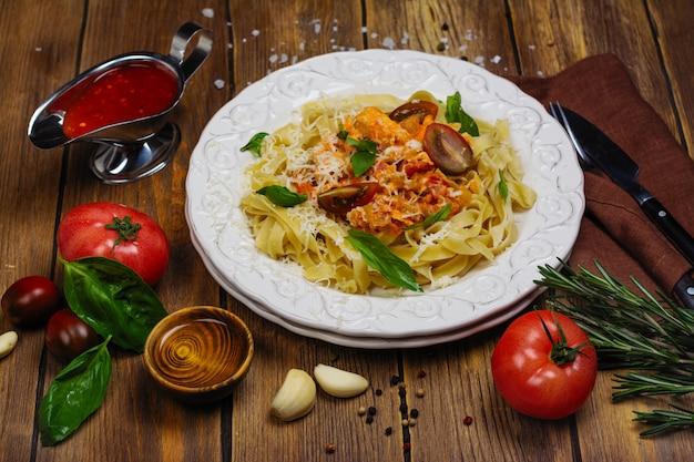 Homemade italian pasta with tomato sauce, chicken, and basil