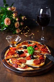 모짜렐라, 페퍼로니 소시지, 올리브와 바질, 테이블에 레드 와인 한 잔을 곁들인 홈 메이드 이탈리아 피자.