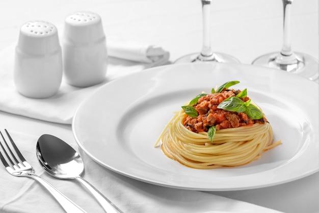 일반 흰색 접시에 볼로냐 소스와 함께 만든 이탈리아 스파게티