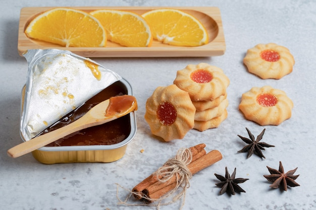 Homemade jam and cookies with orange slices and cinnamon over grey surface.