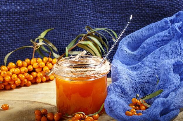 Homemade jam, glass jar with sea buckthorn jam on blue canvas