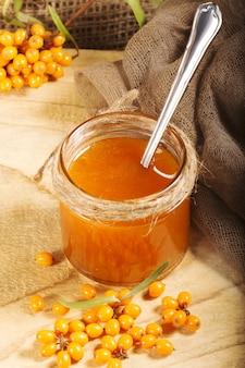 Homemade jam, glass jar with sea buckthorn jam on canvas