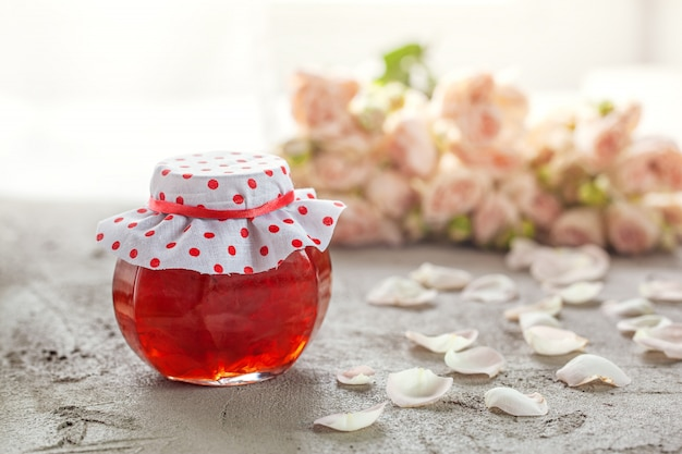 Homemade jam of rose petals on table with bouquet of roses.