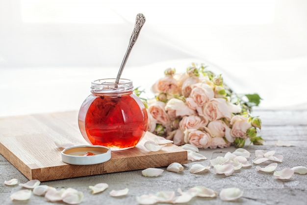 Homemade jam of rose petals on a table with roses bouquet.