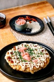 Домашние японские блины из капусты окономияки быстрого питания, украшенные на черной керамической тарелке с палочками для еды и ингредиентами выше.