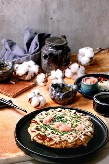 Домашний японский фаст-фуд блинчик из капусты окономияки с луком, маринованным имбирем, соусом майонез на черной керамической тарелке. плоская планировка