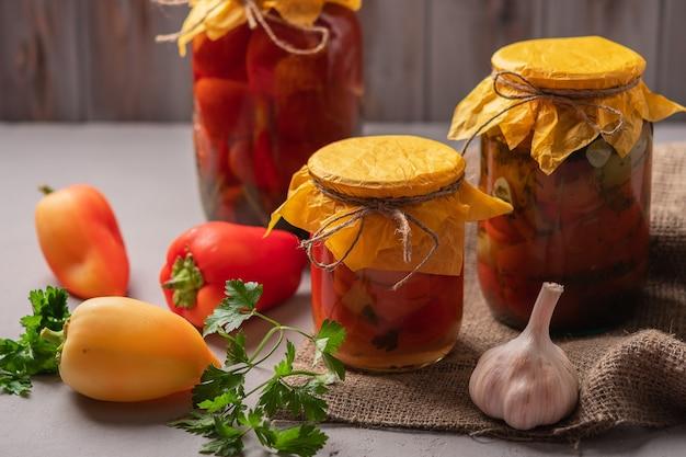 素朴な木製の背景にピクルスとトマトのピクルスと缶詰の自家製の瓶