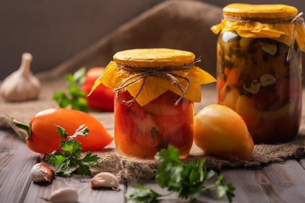素朴な木製の背景に唐辛子のピクルスの自家製の瓶のピクルスと缶詰の製品