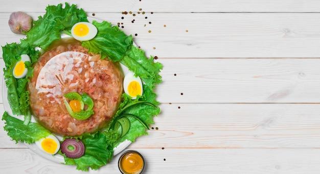 Домашнее желе на белом деревянном столе. вид сверху с копией пространства. желе с мясом или заливным из говядины, традиционное блюдо восточноевропейской кухни.