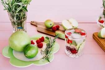 Homemade juice with ingredient on wooden pink backdrop