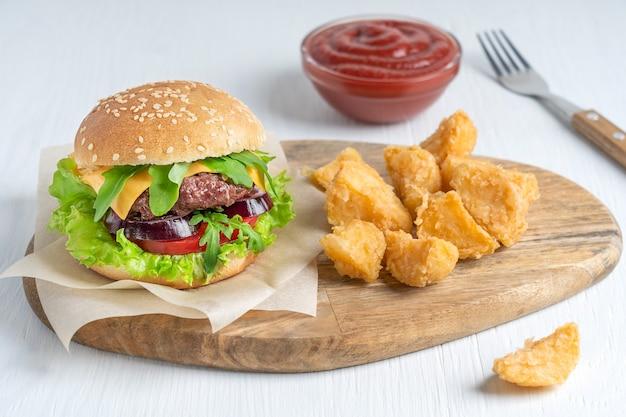 Домашний сочный бургер из жареного мяса, сырного салата и булочки, подается с жареным картофелем