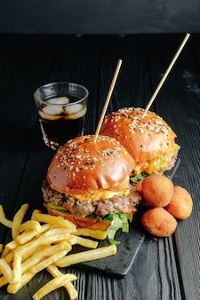 Домашние сочные гамбургеры на деревянной доске, сырные шарики. уличная еда, фастфуд. с картофелем фри и стаканом колы. вид сверху