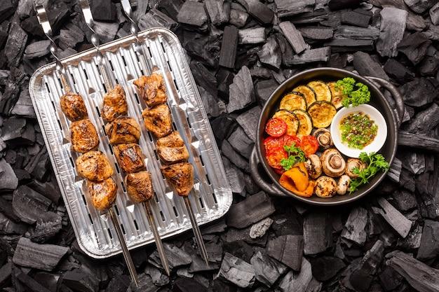 Домашний шашлык и овощи барбекю на сковороде на углях. вид сверху.