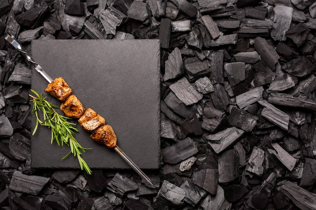 Homemade kebeb on a cutting board with a background of charcoal for barbecue. top view.